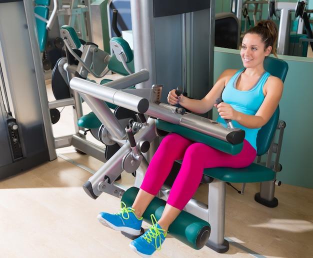 Donna di esercizio della macchina del ricciolo della gamba messa palestra