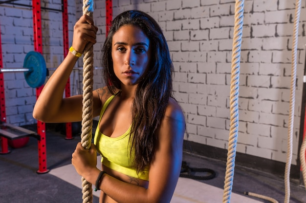 Donna di esercizio di corda di salita in palestra