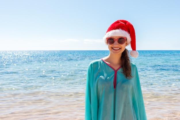 Donna di festa in cappello di santa che si rilassa sulla spiaggia di paradiso, vacanza di natale