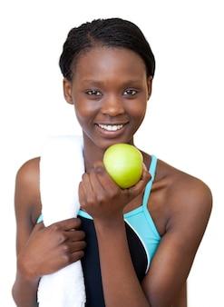 Donna di forma fisica afroamericana che mangia una mela
