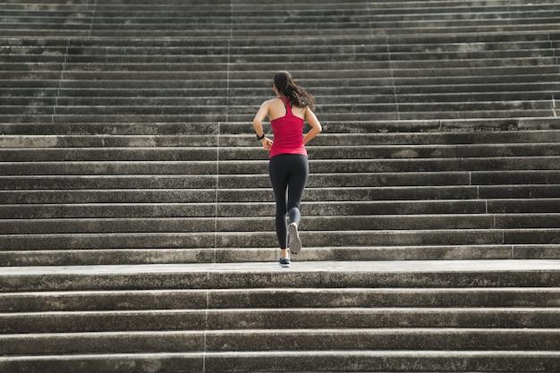 Donna di forma fisica che corre su per le scale