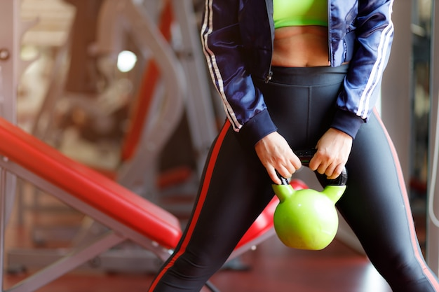 Donna di forma fisica che esercita la campana del bollitore della tenuta del crossfit. allenamento di sollevamento pesi, cross fit e power lifting. sport, concetto di fitness.