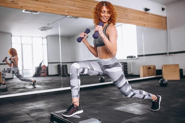 Donna di forma fisica che fa affondi con i dumbbells in palestra