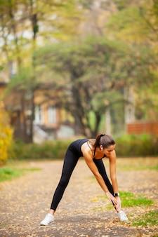 Donna di forma fisica che fa allungando esercizio in parco
