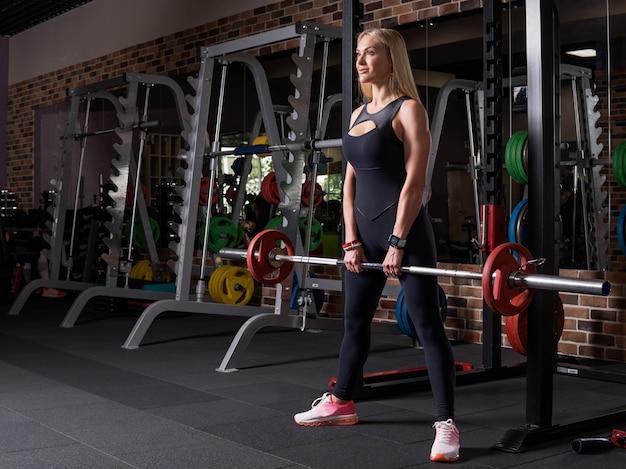 Donna di forma fisica che fa esercizio deadlift in palestra