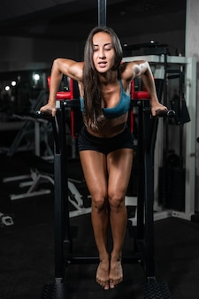 Donna di forma fisica che fa flessioni sulle barre irregolari nella palestra del crossfit