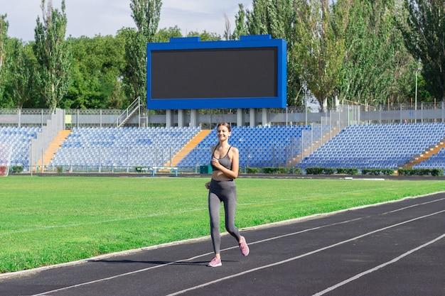 Donna di forma fisica che funziona sulla pista in stadio. allenamento in estate.