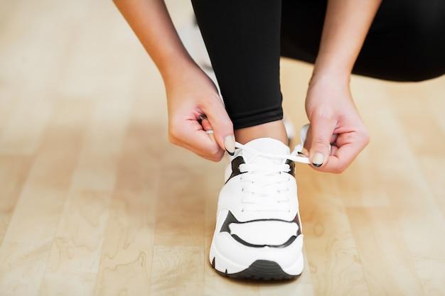 Donna di forma fisica che lega la corda delle scarpe da tennis. tema di abbigliamento sportivo e moda