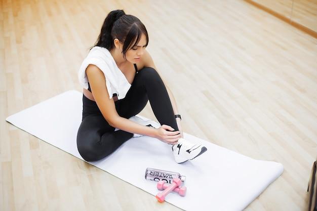 Donna di forma fisica che lega la corda delle scarpe da tennis.