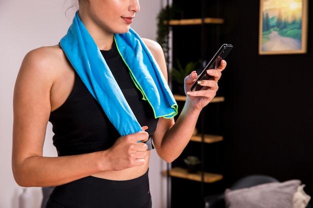 Donna di forma fisica che per mezzo del telefono cellulare