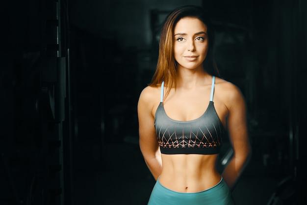 Donna di forma fisica che pompa su allenamento dei muscoli in palestra