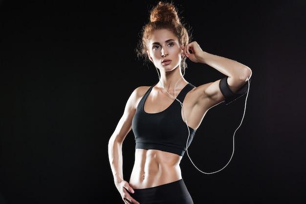 Donna di forma fisica che posa e che ascolta la musica