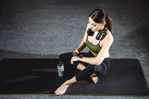 Donna di forma fisica che riposa dopo l'allenamento in palestra