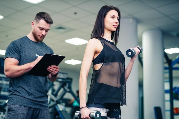 Donna di forma fisica che si esercita con l'istruttore di forma fisica in palestra.