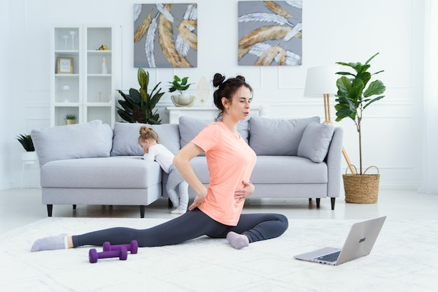 Donna di forma fisica che si esercita sul pavimento a casa e guarda video di fitness in un laptop. bella ragazza facendo allenamento fitness online.
