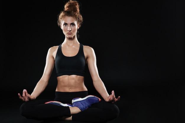 Donna di forma fisica che si siede nella posa e nel meditare del loto