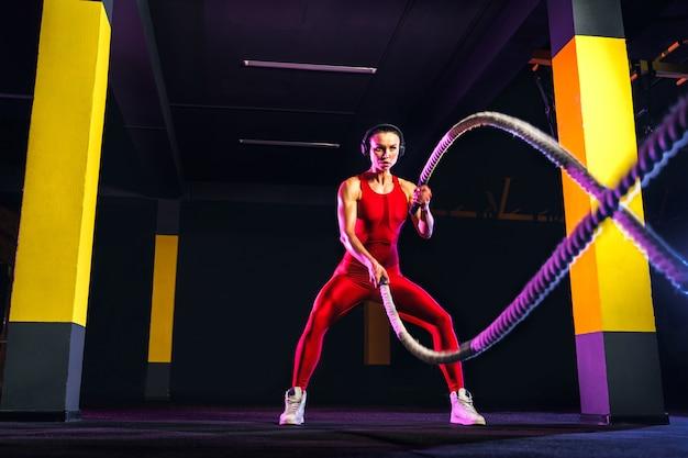 Donna di forma fisica che usando le corde di allenamento per l'esercizio in palestra. atleta che risolve con le corde di battaglia alla palestra trasversale