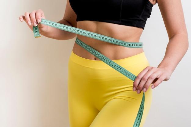 Donna di forma fisica con un nastro di misurazione