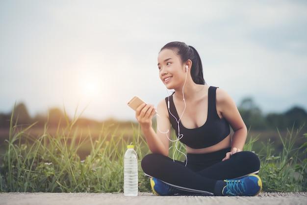 Donna di forma fisica in cuffie ascolto musica durante il suo allenamento ed esercizio nel parco