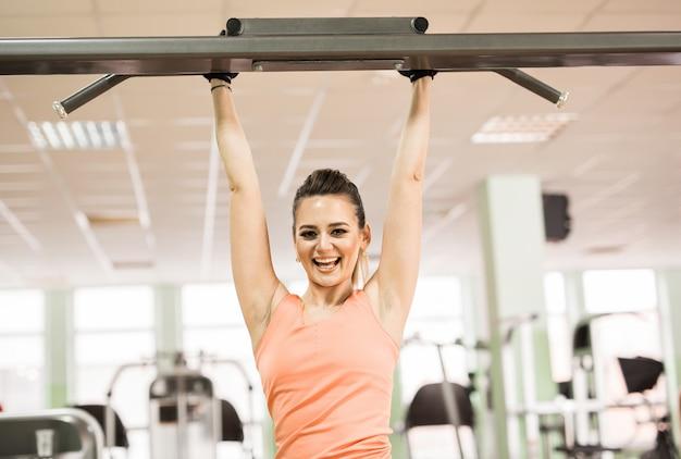 Donna di forma fisica in palestra che si esercita addominali sulla barra orizzontale