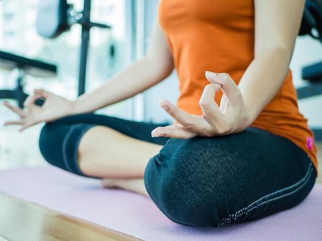 Donna di formazione yoga e meditazione con sfondo attrezzature per il fitness, sport e sano co