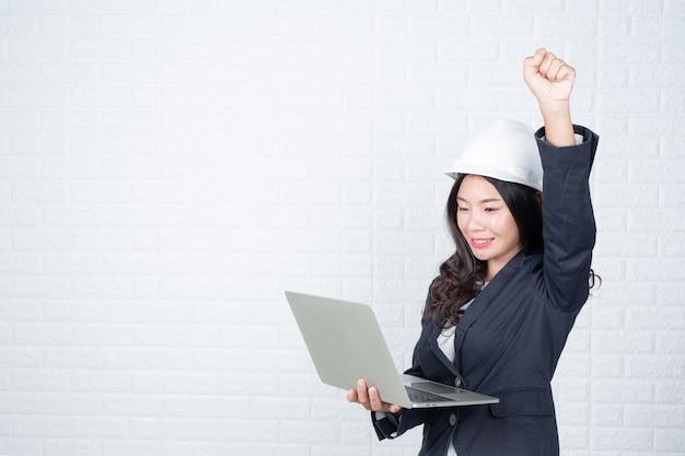 Donna di ingegneria che tiene un taccuino separato, muro di mattoni bianchi fatto gesti con la lingua dei segni.