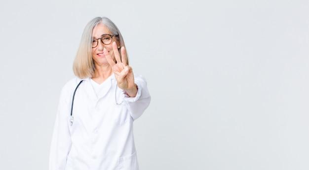 Donna di medico di mezza età che sorride e sembra amichevole, mostrando il numero tre o terzo con la mano in avanti, conto alla rovescia