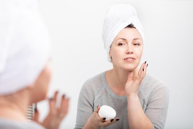 Donna di mezza età che applica crema anti-invecchiamento