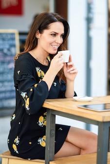 Donna di mezza età che beve il caffè in un bar caffetteria urbana.