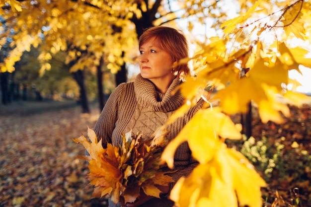 Donna di mezza età che cammina con il mazzo delle foglie di acero nella foresta di autunno. paesaggio autunnale