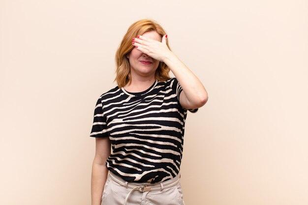 Donna di mezza età che copre gli occhi con una mano sentendosi spaventata o ansiosa, chiedendosi o aspettando ciecamente una sorpresa