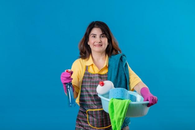 Donna di mezza età che indossa un grembiule e guanti di gomma che tengono spray per la pulizia e bacino con strumenti di pulizia