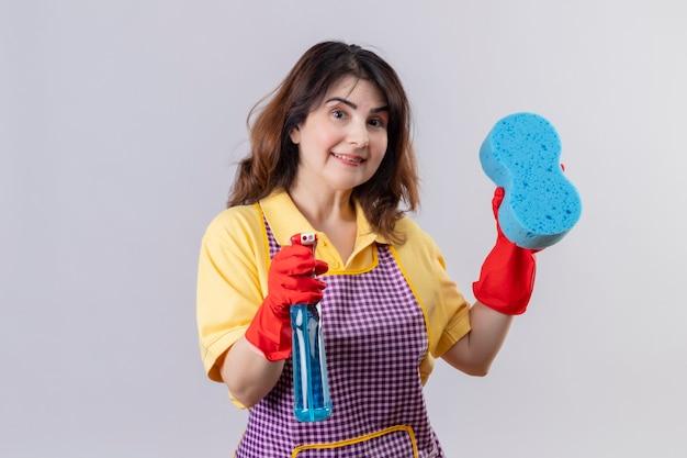 Donna di mezza età che indossa un grembiule e guanti di gomma tenendo spray per la pulizia e spugna