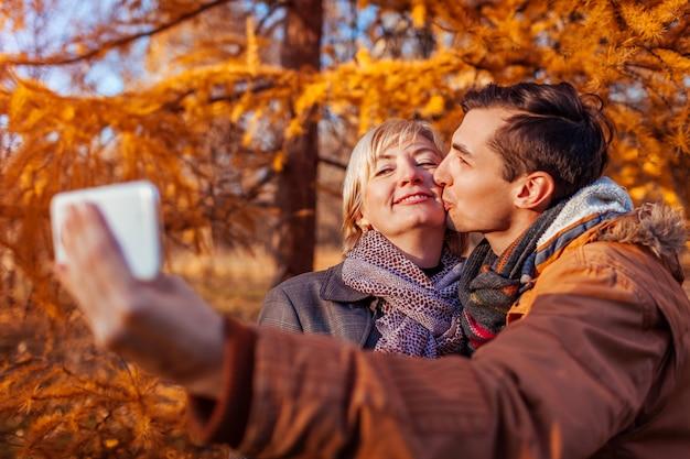 Donna di mezza età che prende selfie con suo figlio adulto che per mezzo del telefono