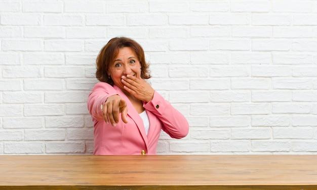 Donna di mezza età che ride di te, indicando la fotocamera e prendendo in giro o deridendoti