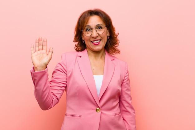 Donna di mezza età che sorride allegramente e allegramente, agitando la mano, dandovi il benvenuto e salutandovi o dicendo addio alla parete rosa