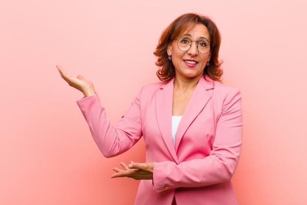 Donna di mezza età che sorride con orgoglio e fiducia, sentendosi felice e soddisfatta e mostrando un concetto sullo spazio della copia contro la parete rosa
