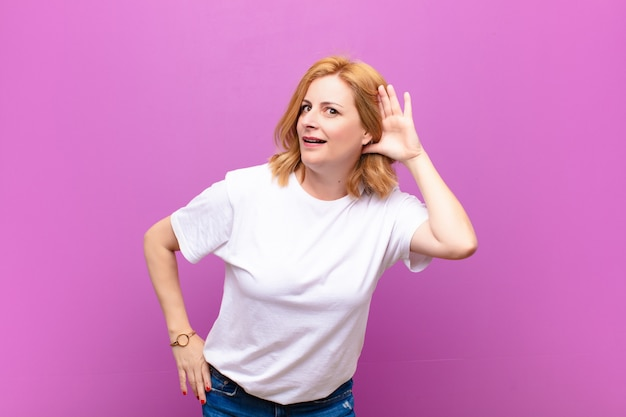 Donna di mezza età che sorride, guarda curiosamente di lato, cerca di ascoltare pettegolezzi o sente un segreto