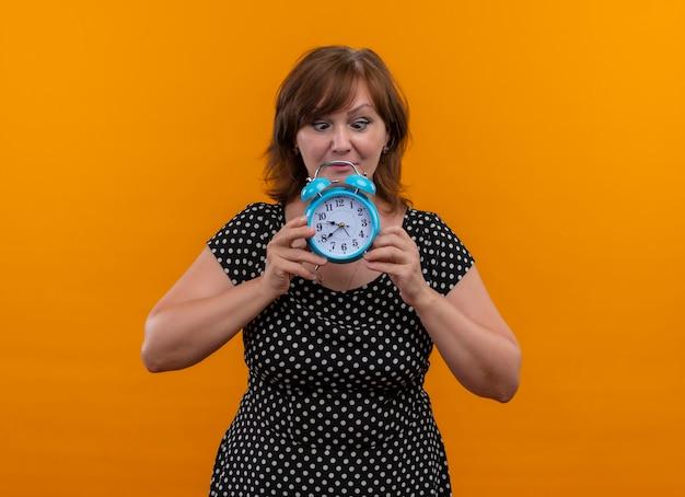 Donna di mezza età che tiene sveglia con gli occhi incrociati sulla parete arancione isolata con lo spazio della copia