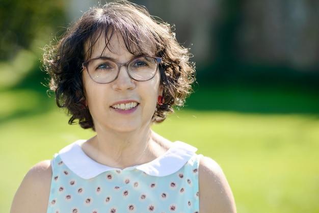 Donna di mezza età con gli occhiali in giardino
