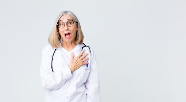 Donna di mezza età dottore sentirsi scioccata e sorpresa, sorridendo, prendendosi per mano, felice di essere quella o mostrando gratitudine