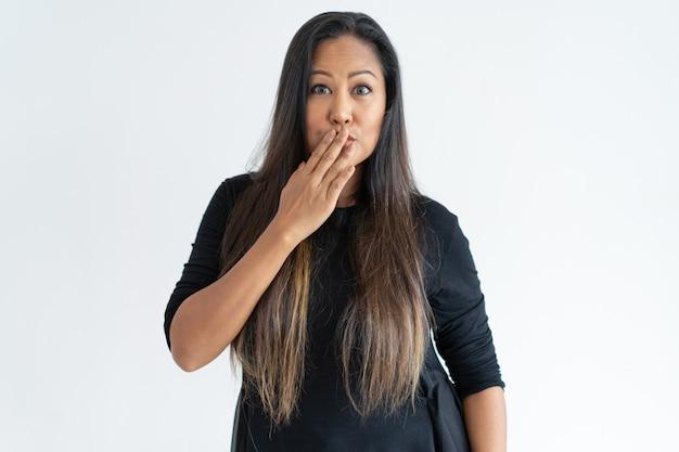 Donna di mezza età imbarazzata che copre la bocca con la mano