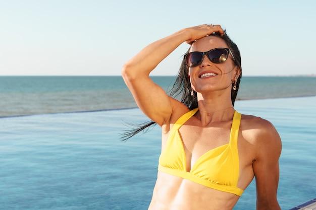 Donna di mezza età in bikini giallo che si siede vicino allo stagno