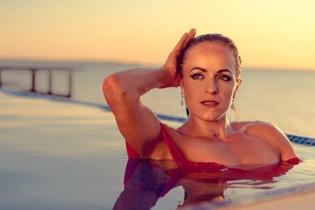 Donna di mezza età in bikini rosso in un'acqua di piscina