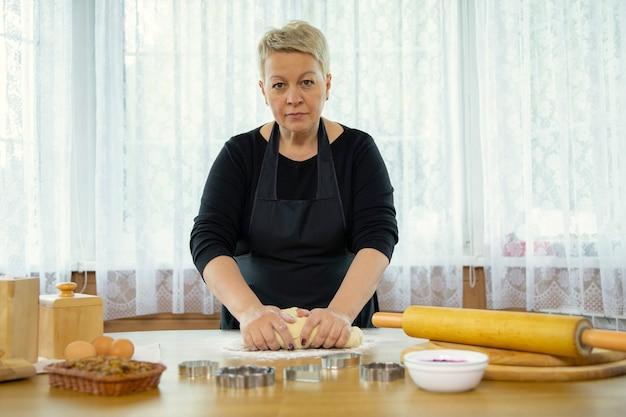 Donna di mezza età in grembiule nero che produce i biscotti casalinghi che schiacciano pasta