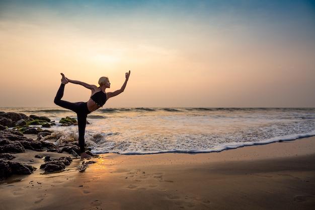 Donna di mezza età in nero facendo yoga sulla spiaggia di sabbia in india posa di natarajasana