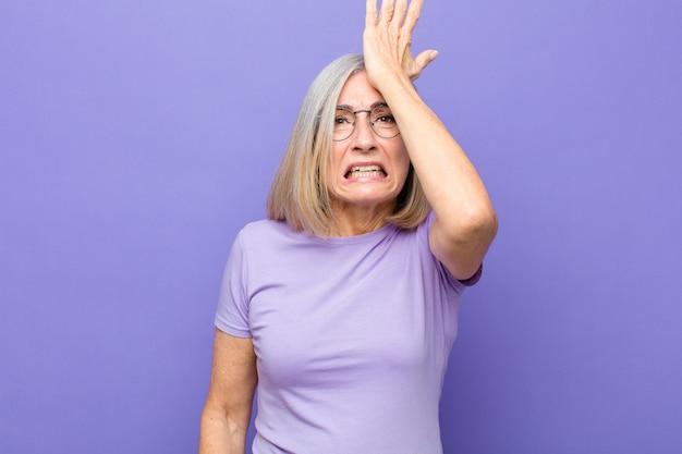 Donna di mezza età o di mezza età che solleva il palmo alla fronte pensando oops, dopo aver fatto uno stupido errore o aver ricordato, sentendosi stupida