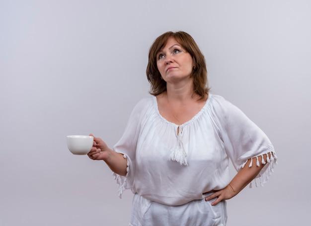 Donna di mezza età premurosa che tiene tazza di tè che osserva in su sulla parete bianca isolata