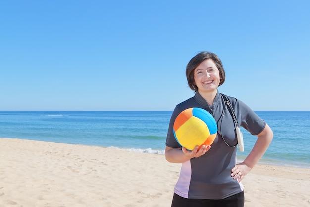 Donna di mezza età sulla spiaggia con una palla da pallavolo. avvicinamento.