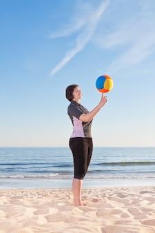 Donna di mezza età sulla spiaggia con una palla da pallavolo giocando. avvicinamento.